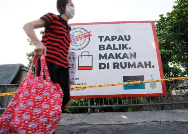 A woman wearing a mask in Jalan Paya Terubong, George Town, walks past a signboard urging to public to pack food to consume at home. Sunpix by MASRY CHE ANI