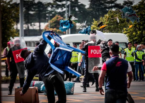 Light Strike Force (LSF) police personnel clash with protesters during the Ops Foxtrot Zulu KLIA 2019 training session at the KLIA cargo complex. ASHRAF SHAMSUL/THESUN