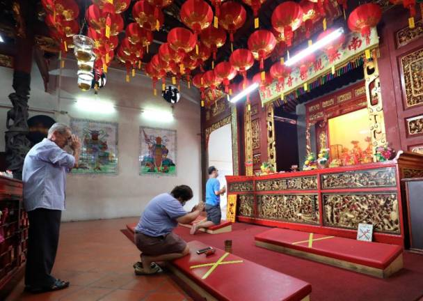 Devotees pray while observing social distancing at the Kuan Yin Temple in Penang yesterday as places of worship reopen to the public after the recovery movement control order took effect on June 10. – MASRY CHE ANI/THE SUN