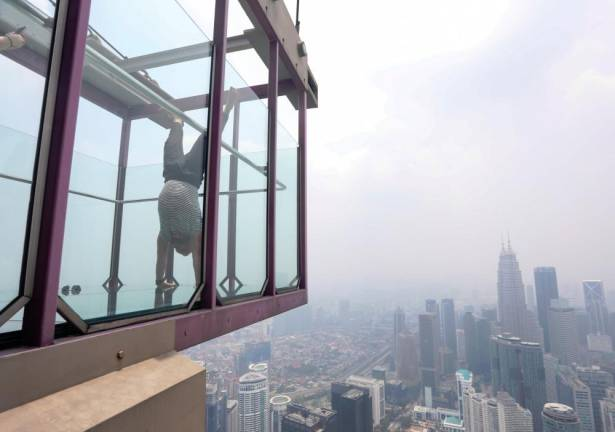 A tourist taking a photo of the panoramic view of the city from Sky Box at KL Tower, amidst the ongoing haze . Asyraf Rasid / the sun