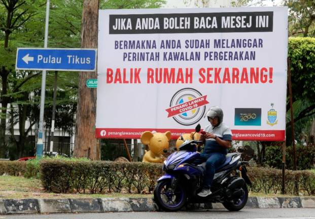 "WHY WAIT... A motorcyclist stops in front of a ""Go home now"" signboard in Jalan Pangkor on of the many erected in Penang by state government to remain the public to stay at spread of Covid-19 infection under the movement control order. SUNPIX BY MASRY CHE ANI"