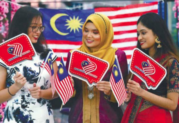 PATRIOTIC POWER... Tenaga Nasional Berhad Seberang Jaya branch employees in traditional attire participating in a 'Fly the Jalur Gemilang' campaign held in conjunction with the nation's 63rd Merdeka Day celebrations. MASRY CHE ANI/THE SUN