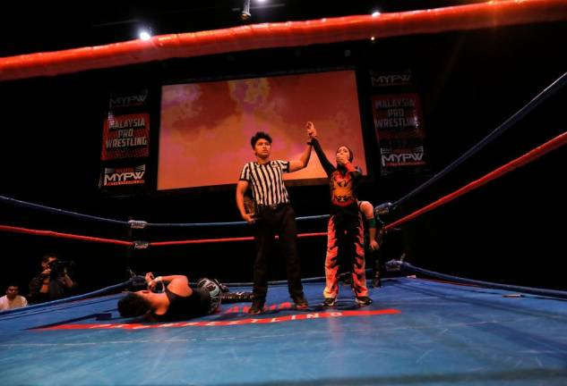 The refree raises Phoenix's hand as the new and first female MyPW Wrestlecon Champion. Asyraf Rasid / the sun