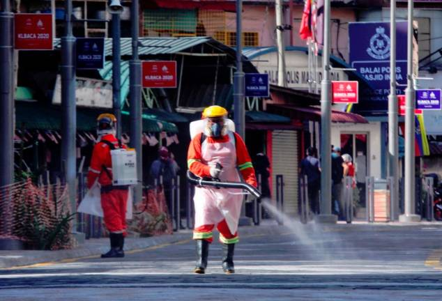 Kuala Lumpur City Hall workers disinfecting areas near the Selangor Mansion and Malayan Mansion flats in Jalan Masjid India after the two buildings were placed under an enhanced movement control order following the discovery of 15 Covid-19 cases there. SUNPIX BY ZAHID IZZANI