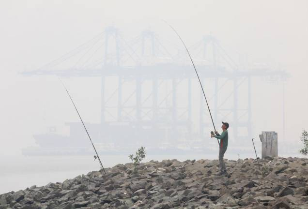 A man is seen fishing at a jetty in Port Klang on Sept 16, 2019 amidst the ongoing haze, as a ship is seen passing by on the background. Asyraf Rasid /TheSun