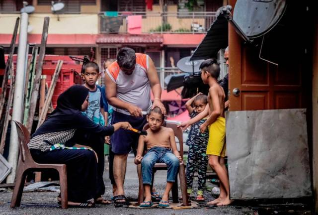 A man giving his son a 'homemade haircut' while his family watches. The government earlier considered allowing barbers and hairdressers to operate during the movement control order, but later decided against it. Sunpix by ZAHID IZZANI.