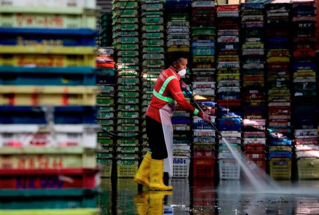 A worker using a high-powered water jet to clean the poultry section at the Selayang wholesale market in Selangor as part of new standard operating procedures to curb the spread of Covid-19.