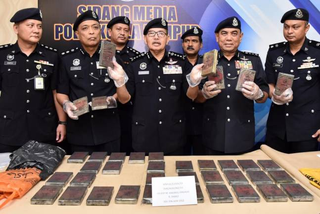Kuala Lumpur police chief Datuk Seri Mazlan Lazim shows drugs believed to be the Base Heroin weighing at 14,470 grams that was sezied from two men in Jalan Dutamas Solaris on 20 June.