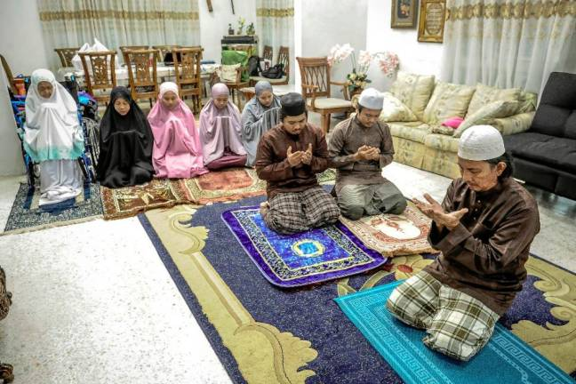 A Muslim family performing Terawih prayers at home as mosque will remain close throughout the movement control order period. Sunpix by ADIB RAWI YAHYA.