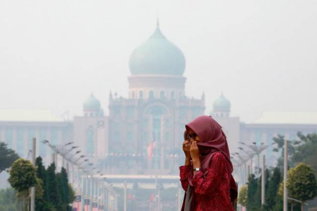 A woman covers her face with a scarf in front of the Malaysia's Prime Minister's office, which is shrouded in haze, in Putrajaya, Malaysia, September 17, 2019. REUTERS PIX