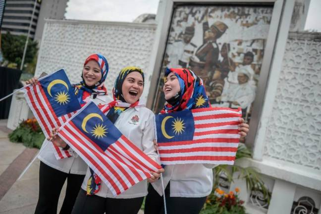 PATRIOTIC PITCH... Three members of the City Hall choir display the Jalur Gemilang againts a backdrop of the country's first prime minister Tunku Abdul Rahman, during the launch of a fly-the-flag event in Kuala Lumpur ahead of Merdeka Day on Aug 31. ADIB RAWI YAHYA/THE SUN