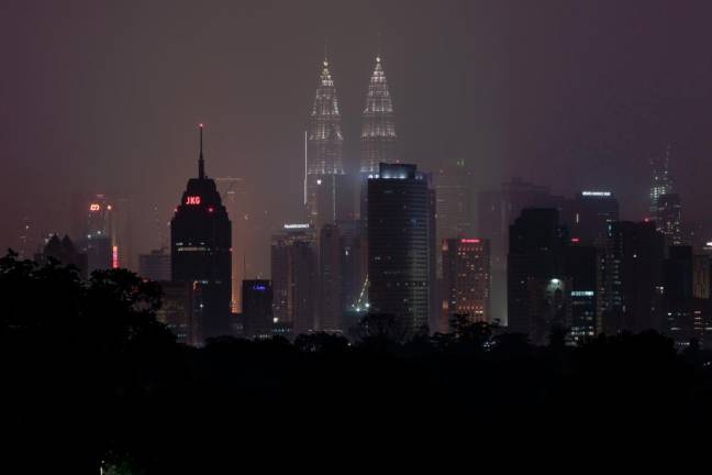 Malaysia's capital skyline with the Petronas Twin Towers (L) and Kuala Lumpur Tower (R) landmarks is blanketed by haze in Kuala Lumpur on September 18, 2019. Toxic haze from Indonesian forest fires closed thousands of schools across the country and in neighbouring Malaysia on September 18, while air quality worsened in Singapore just days before the city's Formula One motor race. AFP PIX