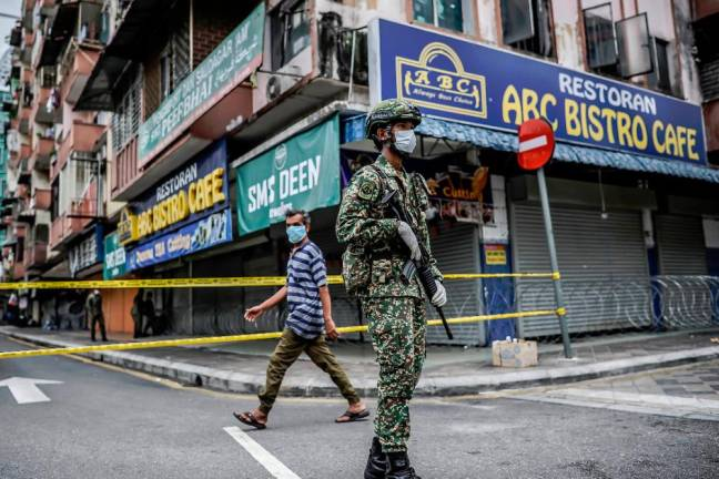 Armed forces control the in and out of residents following the discovery of the COVID-19 case at the Malayan Mansion, Kuala Lumpur. ADIB RAWI YAHYA/THESUN