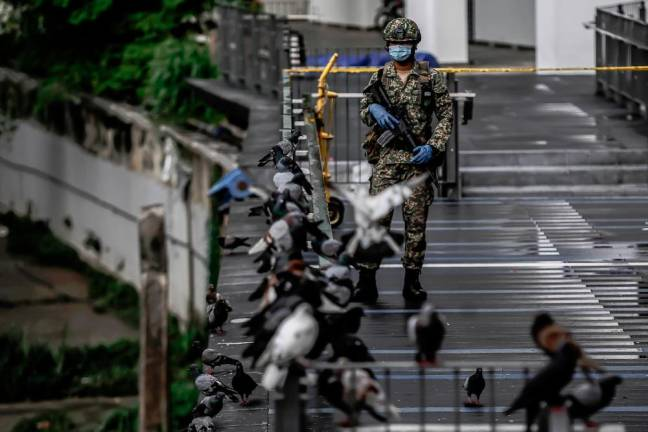 LOCKED DOWN... A soldier stands guard near a building cordoned off the due to high incident of Covid-19 cases, in Kuala Lumpur. SUNPIX BY ADIB RAWI YAHYA