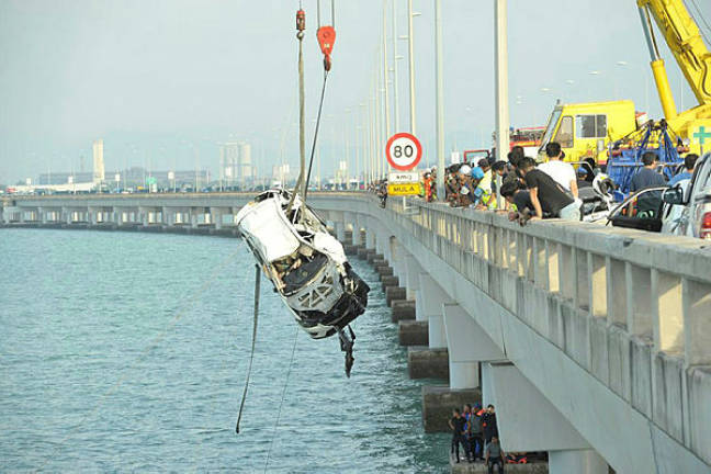 The SUV that fell off the Penang Bridge being recovered by rescue personnel.