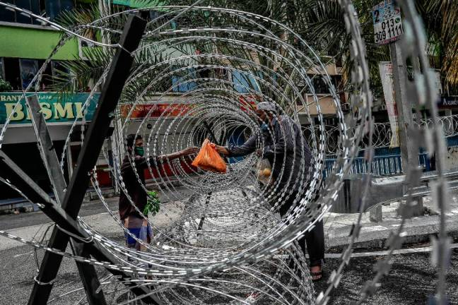 A resident being given food through barbed eires near the Selayang wholesale market. The area has been locked down under an enhanced movement control order. SUNPIX BY ADIB RAWI YAHYA