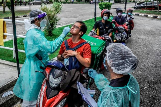 Food delivery riders queue to have oral swabs taken by health workers wearing protective suits in Shah Alam as part of the latest procedures to curb the spread of Covid-19. Sunpix by ADIB RAWI YAHYA