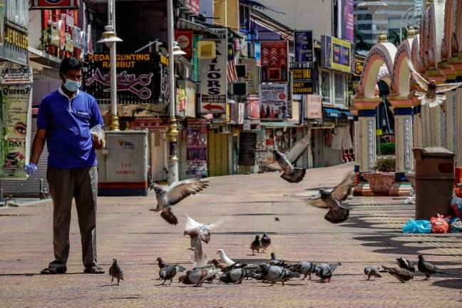 ACT OF KINDNESS... A men feeds pigeos at Kuala Lumpur alley which is devoid of people due to the movement control order. SUNPIX BY ADIB RAWI YAHYA