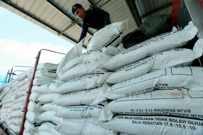 Domestic Trade and Consumer Affairs (KPDNHEP) officer checks subsidized rice fertilizer believed to be smuggled to a factory in Sedaka, Yan, Kedah. BBXpress