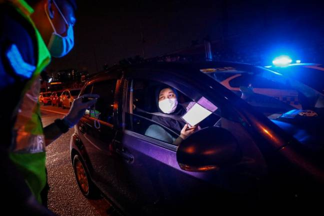 A woman showing a company letter certifying she is an employee after being stopped at a roadblock. SUNPIX BY HAFIZ SOHAIMI.
