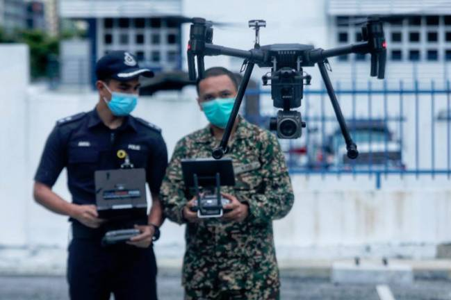 Police and army personnel in Kuala Lumpur testing one of the drones that would be used to monitor the situation on the ground during movement control order period. SUNPIX BY ZAHID IZZANI