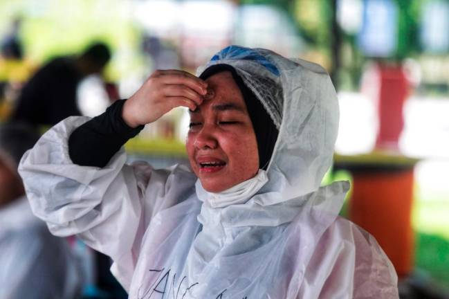 A health worker on break rubs and ice cube on her forehead during her deployment in Gombak, Selangor to conduct mass-testing for Covid-19 on residents in the area. Sunpix by ZAHID IZZANI.