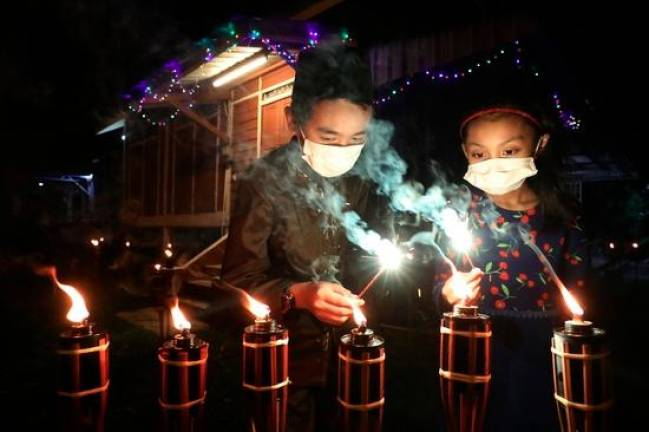 FESTIVE LAMPS... Muhammad Irfan Danial Muhammad Saad (left) and Tasnim Daud lighting outside their kampung house near Kulim in Kedah. MASRY CHE ANI/THE SUN