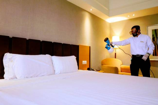 Five star hotel staff routinely disinfects a room. ASYRAF RASID/THE SUN