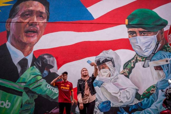 TRIBUTE TO HEROES... A couple takes a picture against the backdrop of a mural in Kuala Lumpur dedicated to the frontliners fighting the Covid-19 pandemic. ADIB RAWI YAHYA/THESUN