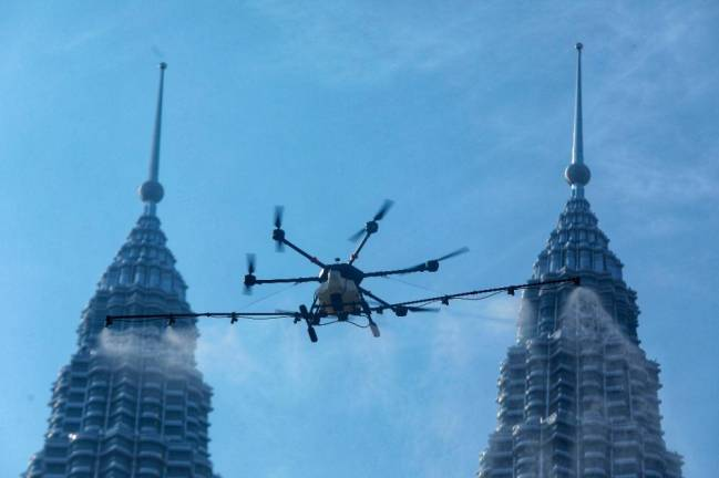 SPRAYING FROM ABOVE... A drone with a 16-litre capacity being used to disinfect fall building in Kuala Lumpur. SUNPIX BY ZAHID IZZANI.