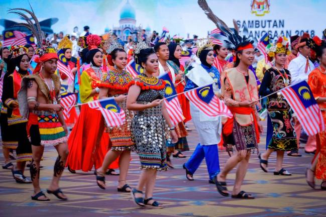 Students dressed in cultural clothes wave their flags during the 61st Merdeka Day celebration in Putrajaya last year. KAMARIDUAN MOHD NOR/THE SUN