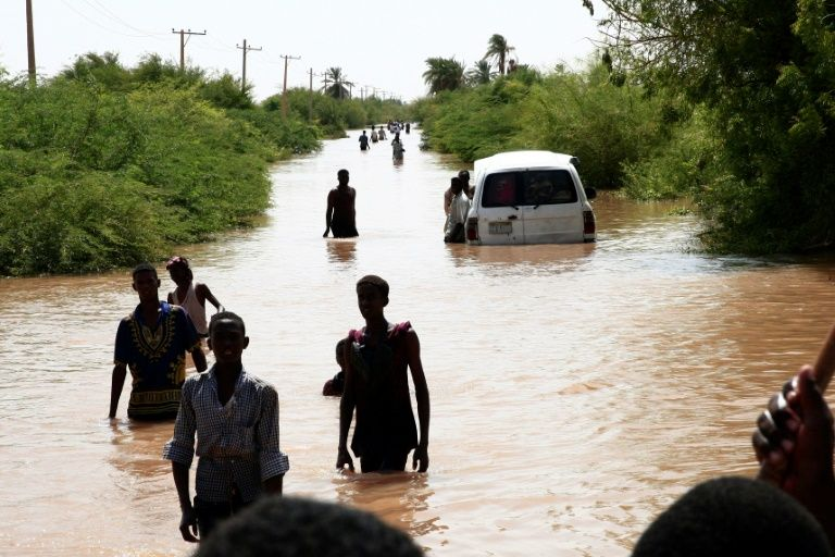 Sudanese people walk a flooded road in Wad Ramli village on the eastern banks of the Nile river. — AFP