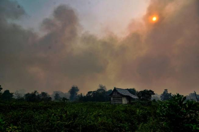 Thick smoke from a forest fire nearly covers the sun over Pekanbaru in Riau province on September 18, 2019. Toxic haze from Indonesian forest fires closed schools and airports across the country and in neighbouring Malaysia on September 18, while air quality worsened in Singapore just days before the city's Formula One motor race.