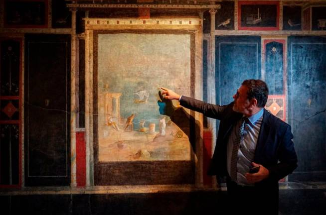 "This undated photo handout on February 18, 2020 by the press office of the Archaeological Site of Pompeii shows a curator showing fresco in the ""House of Orchards"" during the reopening of three ""domus"" and conclusion of safety work on the archaeological site of Pompeii. AFP PHOTO / ARCHAEOLOGICAL SITE OF POMPEII"