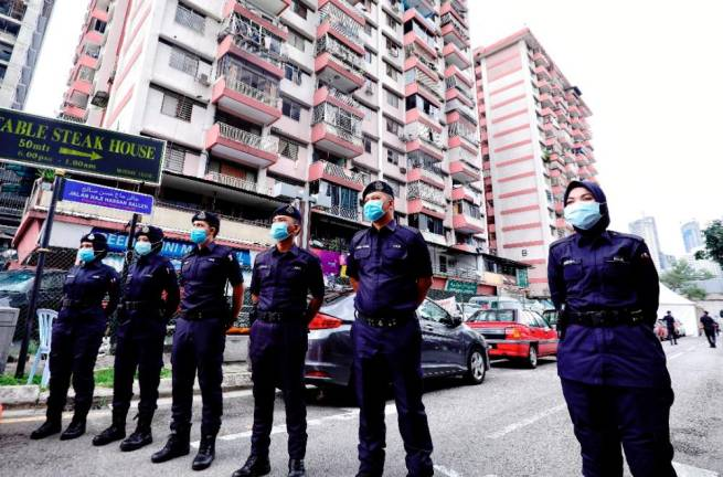 Police standing guard around the PKNS flats in Kampung Baru in Kuala Lumpur as Health Ministry officials conduct Covid-19 checks on residents. Sunpix by ZAHID IZZANI