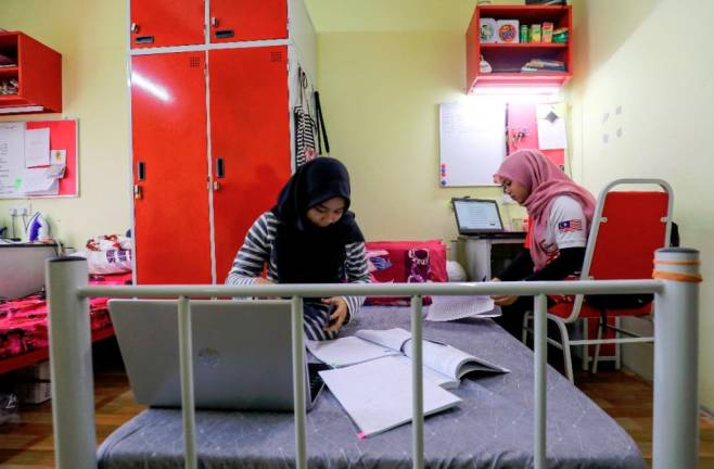 Universiti Teknologi Mara students reviewing notes in their room in Shah Alam following the movement control order, causing lectures to be halted.