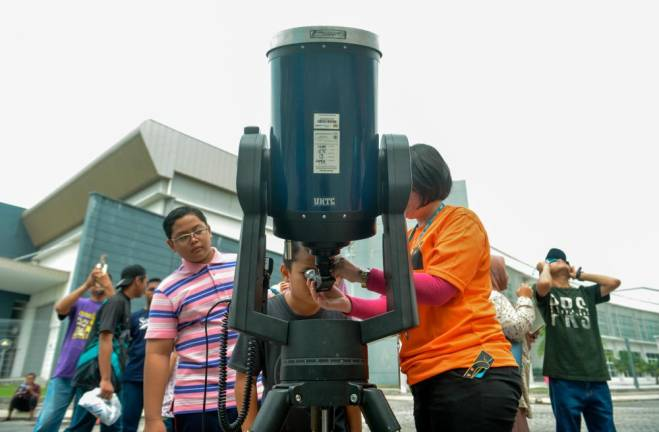 A boy looks at the sun through a telescope during the partial solar eclipse at the Agensi Angkasa Malaysia Complex. Asyraf Rasid / The Sun