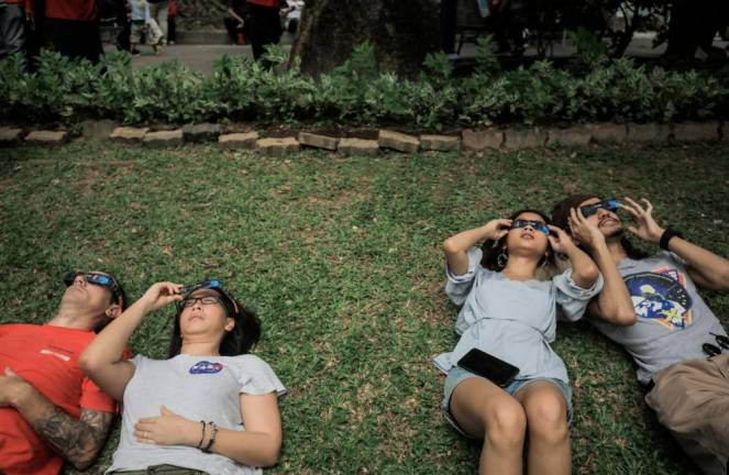 Visitor Demi Maria Sofia and Zarol Zahimi uses a solar filter provided by National Planetarium to see the phenomena of Partial Solar Ecslipe in the grounds of the National Planetarium .AMIRUL SYAFIQ MOHD DIN / THESUN
