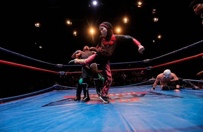 Phoenix delivering a kick to Harry Ray while being suplexed by Shaukat. Asyraf Rasid / the sun