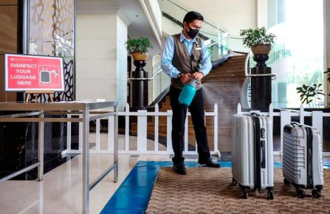 A hotel staff spraying disinfecting on a hotel guest's luggage as part of measures to prevent infection. ASYRAF RASID