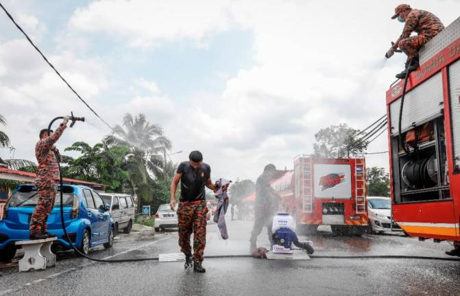 WATER TREATMENT... A firefighter is hosed down by his colleagues after conducting a disinfecting operation at the Sungai Ramal Dalam district in Hulu Langat, Selangor. Sunpix by ASHRAF SHAMSUL AZLAN
