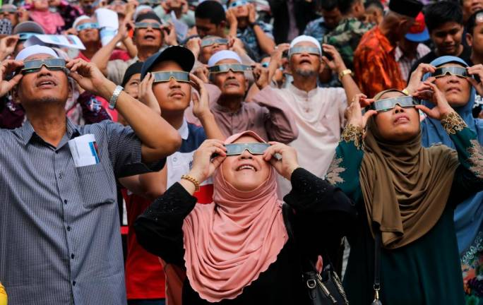 People observe a partial solar eclipse at the Agensi Angkasa Malaysia Complex. Asyraf Rasid /The Sun