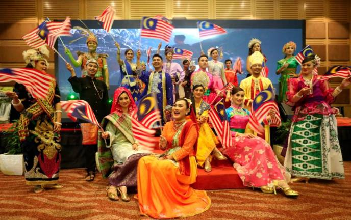 SPLASH OF COLOUR... Performers dressed in traditional attire pose for pictures during Cuti-Cuti Malaysia campaign event at the Putra World Trade Centre in Kuala Lumpur. ASYRAF RASID