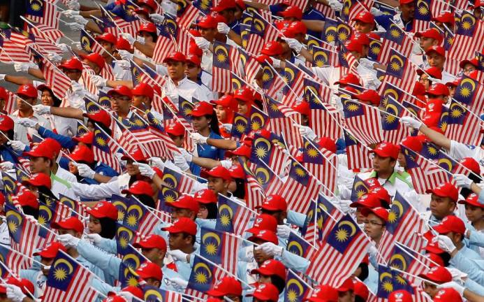 Members from Government Linked Companies (GLC)'s and private sector contigents waving their flags in parade during the 56th National Day celebrations in 2013. Asyraf Rasid/the sun