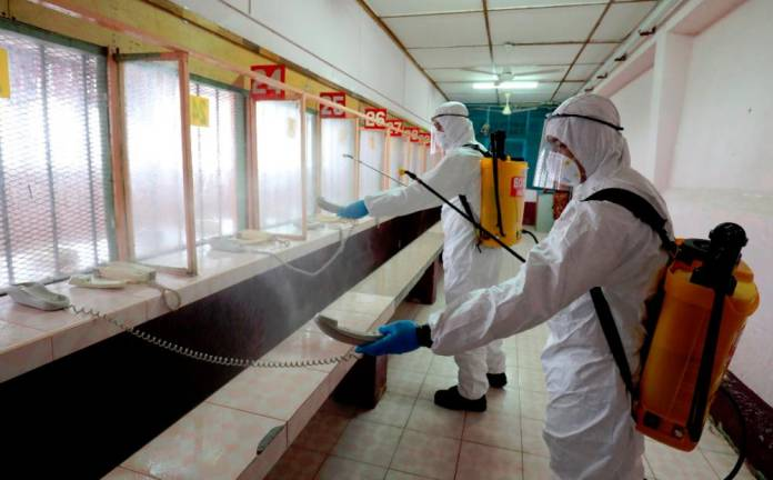 TAKING NO CHANCES... Firefighter in Hazmat suits disinfecting communication equipment and the visitors area of the Penang Prison to prevent the spread of Covid-19. SUNPIX BY MASRY CHE ANI