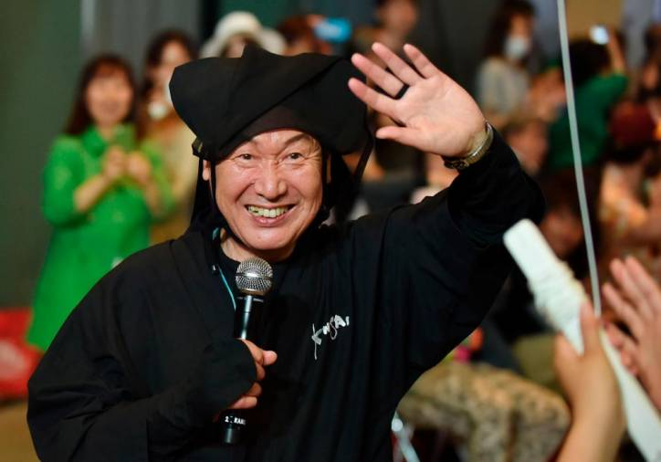 (FILES) This file photo taken on June 12, 2015 shows Japanese designer Kansai Yamamoto waving to the audience after an event in Tokyo. Famed Japanese fashion designer Kansai Yamamoto has died of leukemia at the age of 76, his daughter announced on July 27, 2020. / AFP / Kazuhiro NOGI