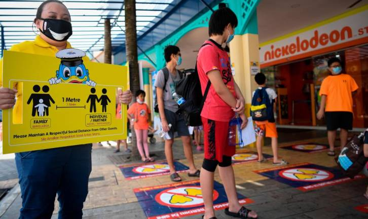 A Sunway Lagoon Theme Park staff holds a a social distancing instruction board to ensure visitors comply with SOPs during the reopening of the theme park after being closed since March 18, following the Covid-19 outbreak. - Bernama