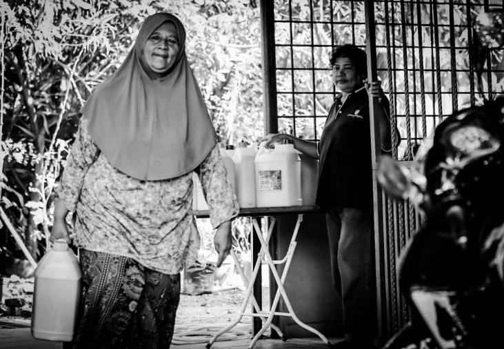 A lady in her 50s bought detergent sold by Azizah at her house. Azizah looks while her customer goes.