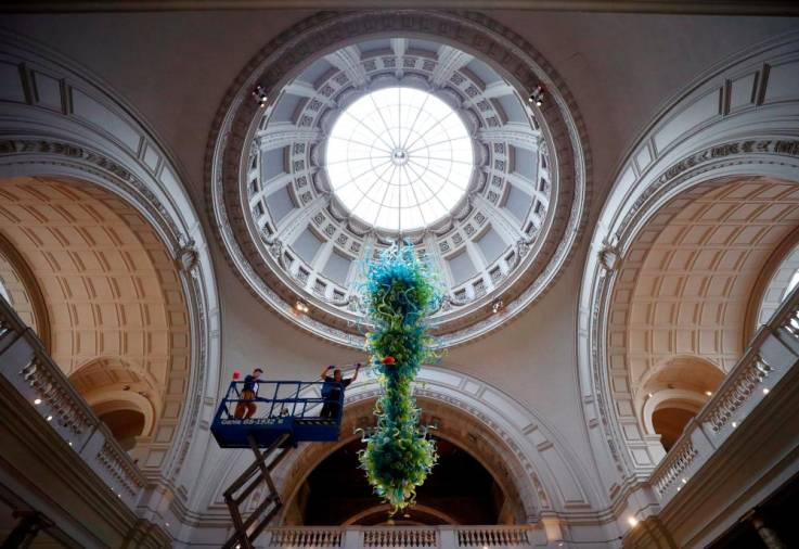 A museum technician cleans the V&A Rotunda Chandelier by Dale Chihuly during preparations to reopen the Victoria & Albert (V&A) Museum, after the outbreak of the coronavirus disease (COVID-19) caused its closure, in London, Britain, August 4, 2020. Picture taken August 4, 2020. REUTERS/Hannah McKay