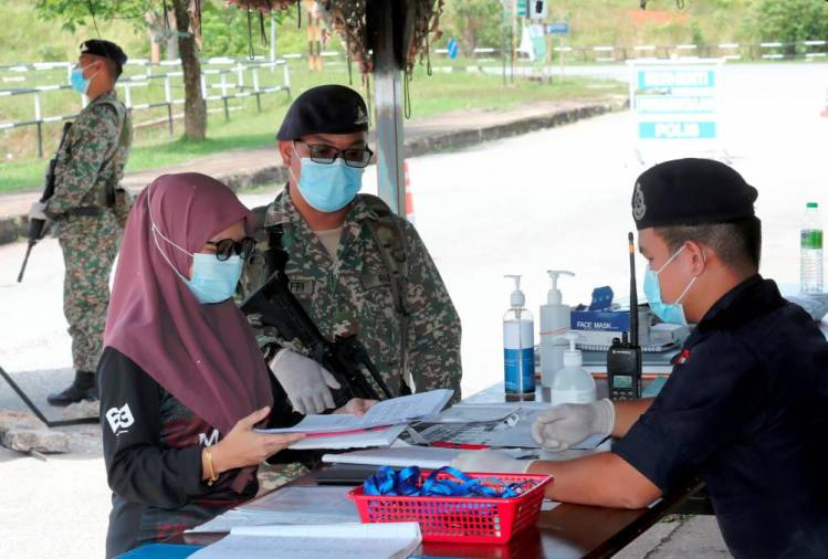 Strict CONTROLS ... A resident of Ambangan Heights in the Kenanga Zone in Aman Jaya, one of the three areas placed under enhanced movement control order in Kedah since Aug 28, shows a medical treatment appointment letter to a policeman at a roadblock at Lebuh Kenanga yesterday. - MASRY CHE ANI/THESUN